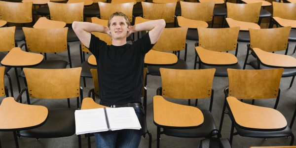 Last student left in college lecture hall --- Image by © Erik Isakson/Tetra Images/Corbis